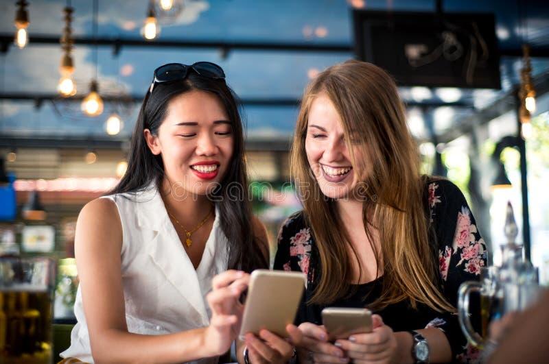 Vrouwelijke vrienden die telefoon in het restaurant met behulp van stock foto