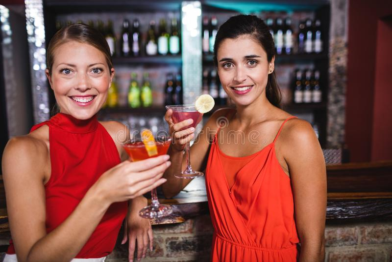 Vrouwelijke vrienden die van cocktail genieten bij teller in nachtclub stock afbeelding