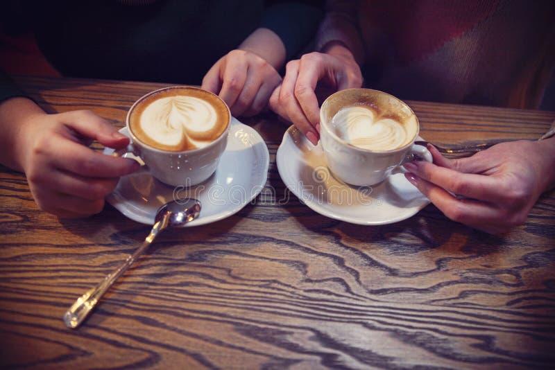 Vrouwelijke vriendenhanden die koppen van koffie houden stock afbeelding