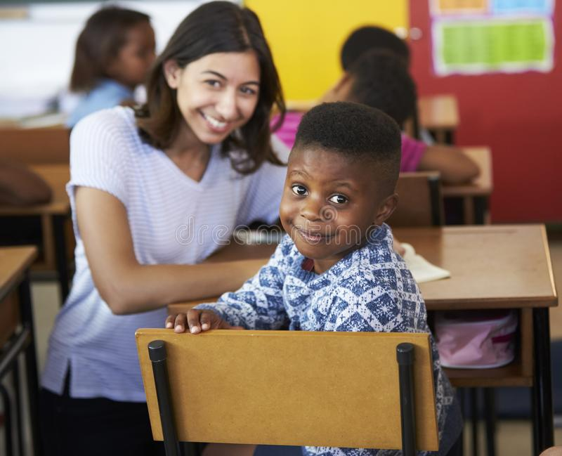 Vrouwelijke Vrijwilligersleraar en basisschooljongen die aan camera glimlachen stock foto