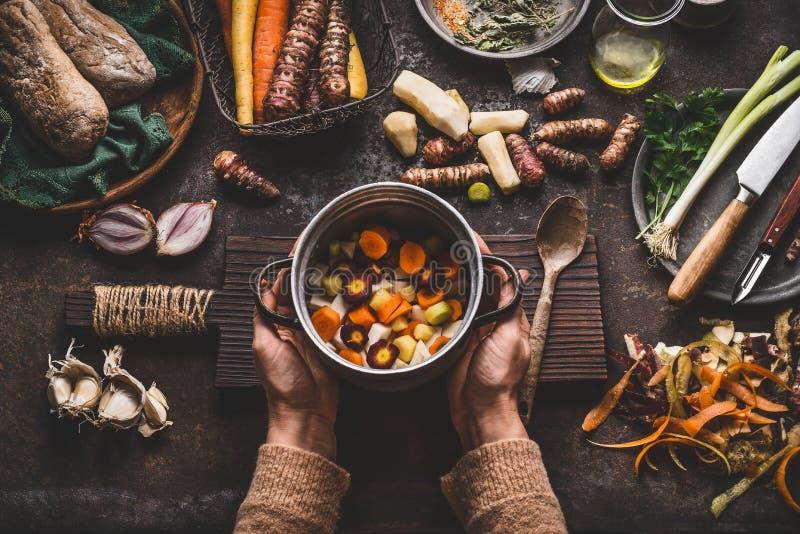 Vrouwelijke vrouwenhanden die pan met gedobbelde kleurrijke groenten op donkere rustieke keukenlijst houden met vegetarische koke stock fotografie