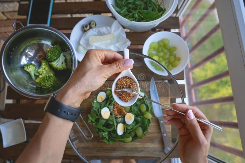 Vrouwelijke vrouwenhanden op houten keukenlijst met groenten die ingrediënten, lepel en hulpmiddelen, hoogste mening, telefoon ko stock foto