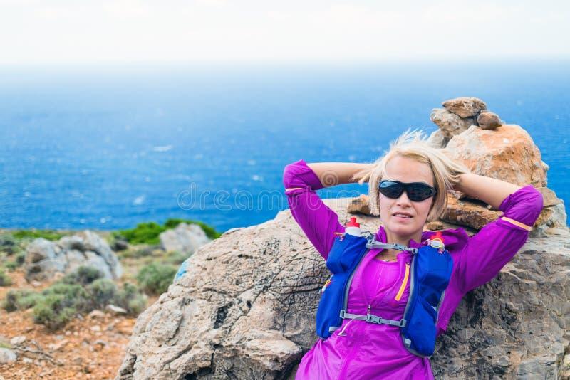 Vrouwelijke wandelaar die op rots, het Eiland van Kreta, Griekenland rusten royalty-vrije stock foto