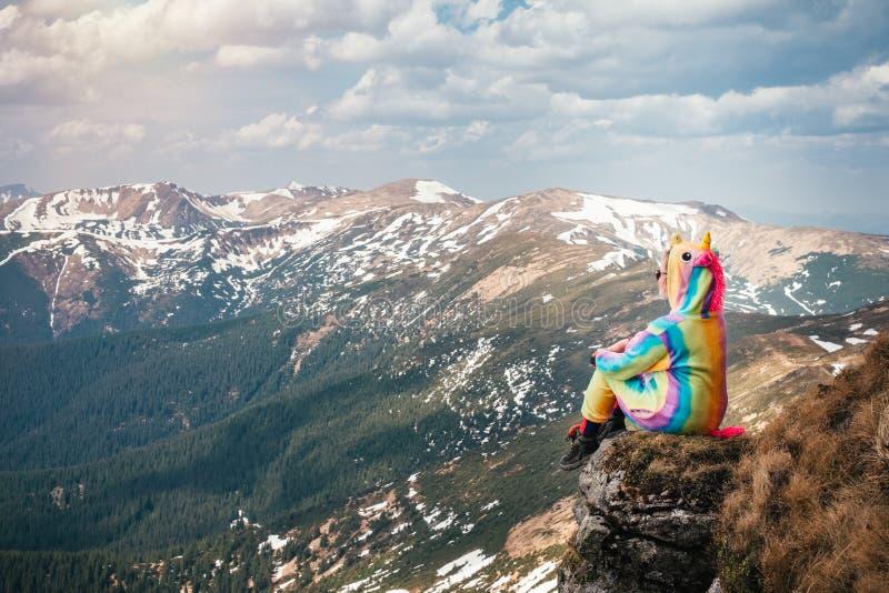 Vrouwelijke wandelaar in een eenhoornkostuum hoog in bergen stock afbeelding