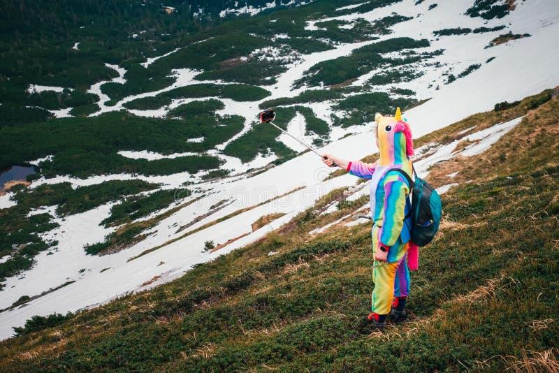 Vrouwelijke wandelaar in eenhoornkostuum die selfie in bergen spreken royalty-vrije stock afbeeldingen