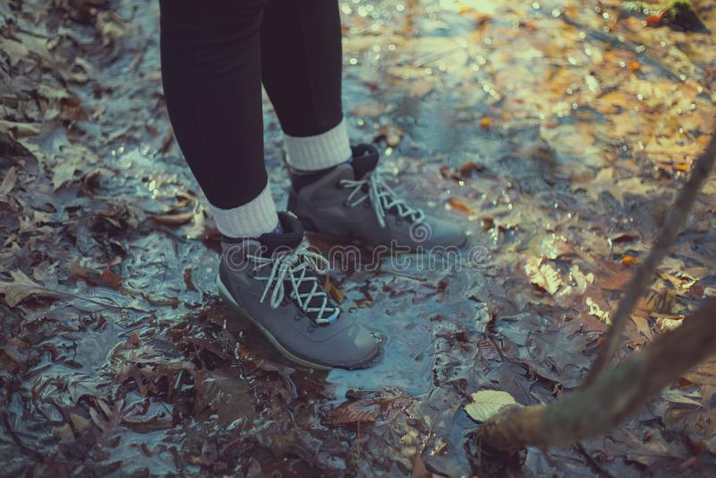 Vrouwelijke wandelaar met laarzen in bladvulklei stock fotografie