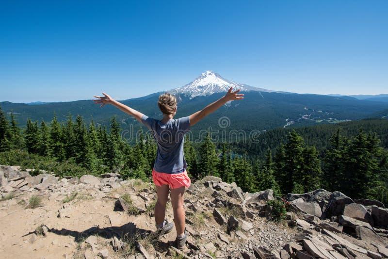 Vrouwelijke wandelaartribunes op de top van Tom Dick en Harry Mountain in MT Hood National Forest, met haar gesteunde wapens, bek royalty-vrije stock foto