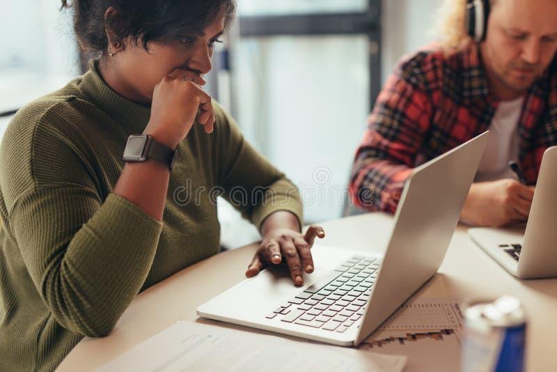 Vrouwelijke werkende laptop van de softwareingenieur bij opstarten stock foto