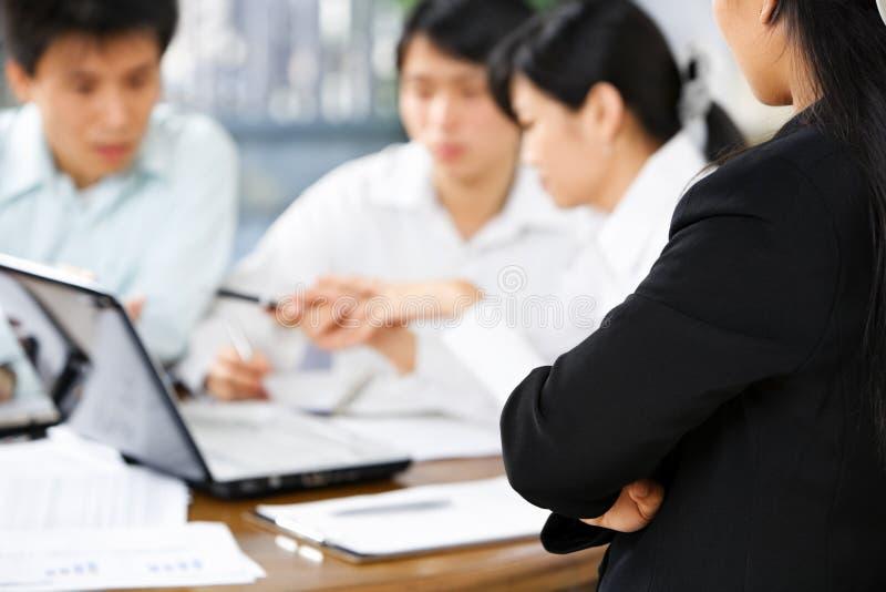 Vrouwelijke werkgever die op haar werknemers het werken let stock foto
