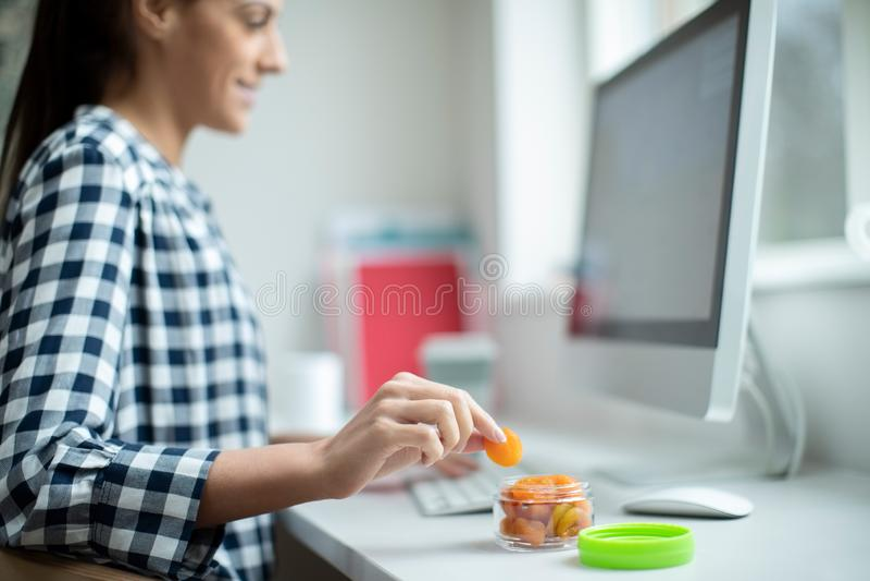 Vrouwelijke werknemer in Bureau die Gezonde Snack van Droge Abrikozen hebben bij Bureau stock fotografie