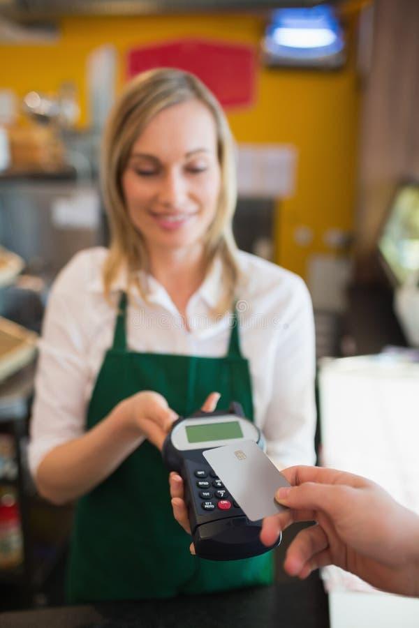 Vrouwelijke werknemer die betaling goedkeuren door creditcard stock fotografie
