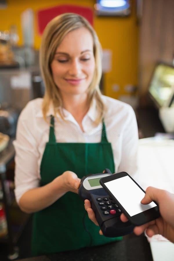 Vrouwelijke werknemer die betaling goedkeuren door NFC stock foto