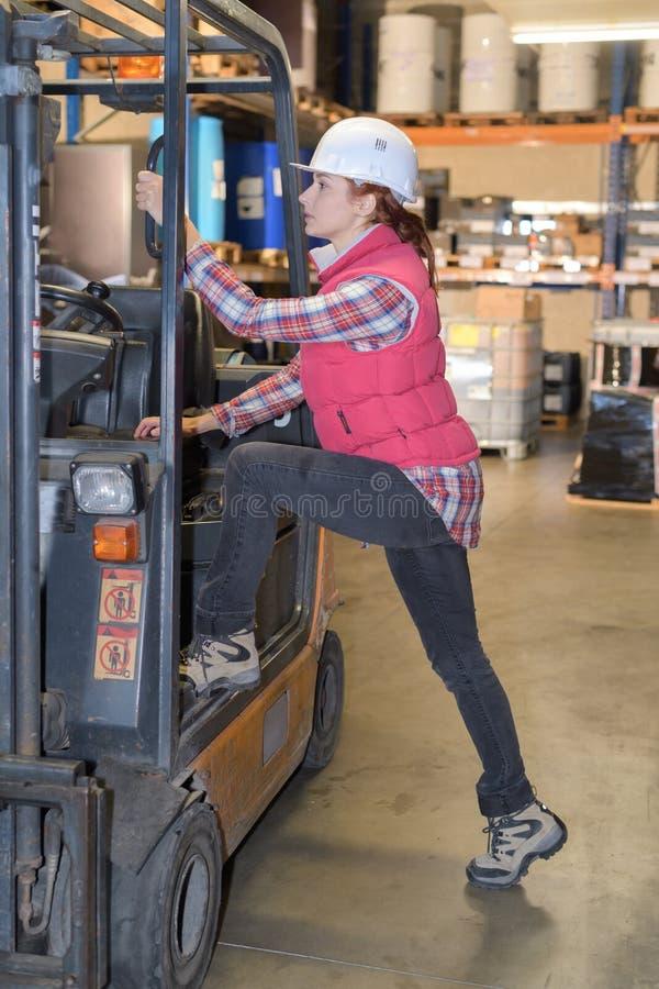 Vrouwelijke werknemer die in cabinevorkheftruck beklimmen stock foto's