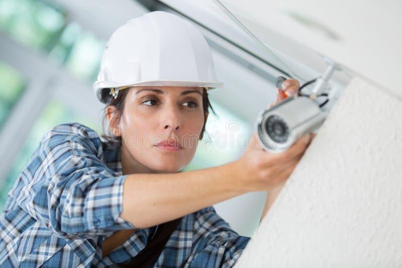 Vrouwelijke werknemer die de camera van veiligheidskabeltelevisie plaatsen in de bureaubouw stock afbeeldingen
