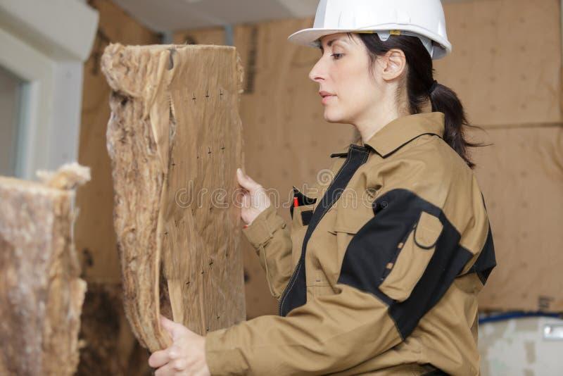 Vrouwelijke werknemer die met isolatieraad werken royalty-vrije stock afbeelding
