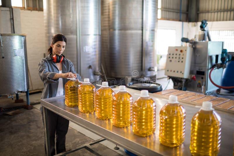 Vrouwelijke werknemer die in oliefabriek werken stock foto's