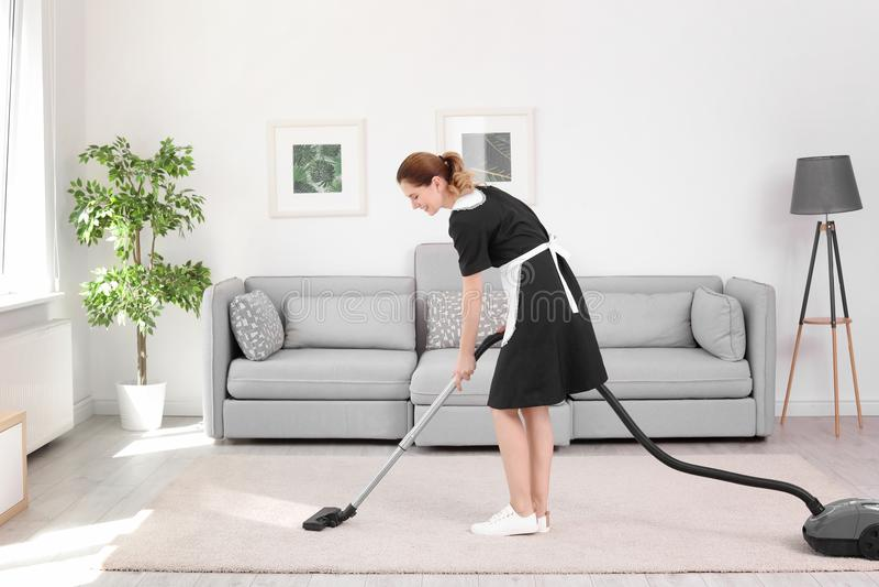 Vrouwelijke werknemer die vuil verwijderen uit tapijt met professionele stofzuiger, binnen stock afbeeldingen