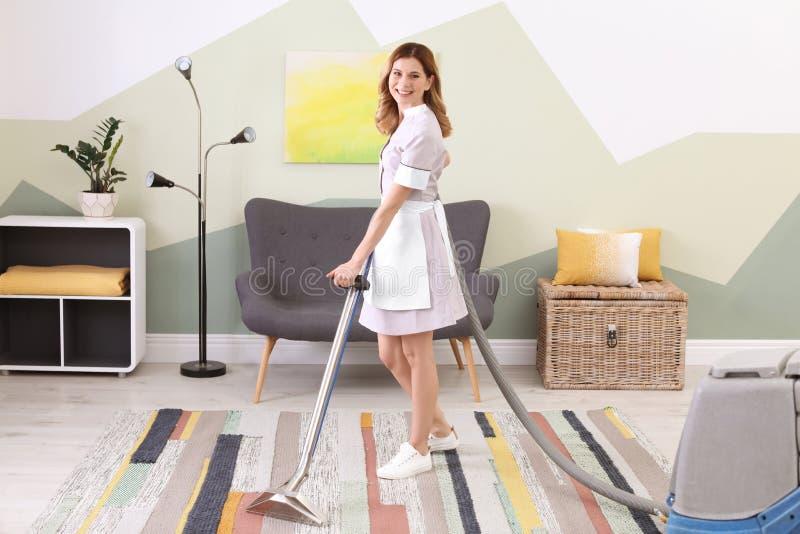 Vrouwelijke werknemer die vuil verwijderen uit tapijt met professionele stofzuiger, binnen stock afbeelding