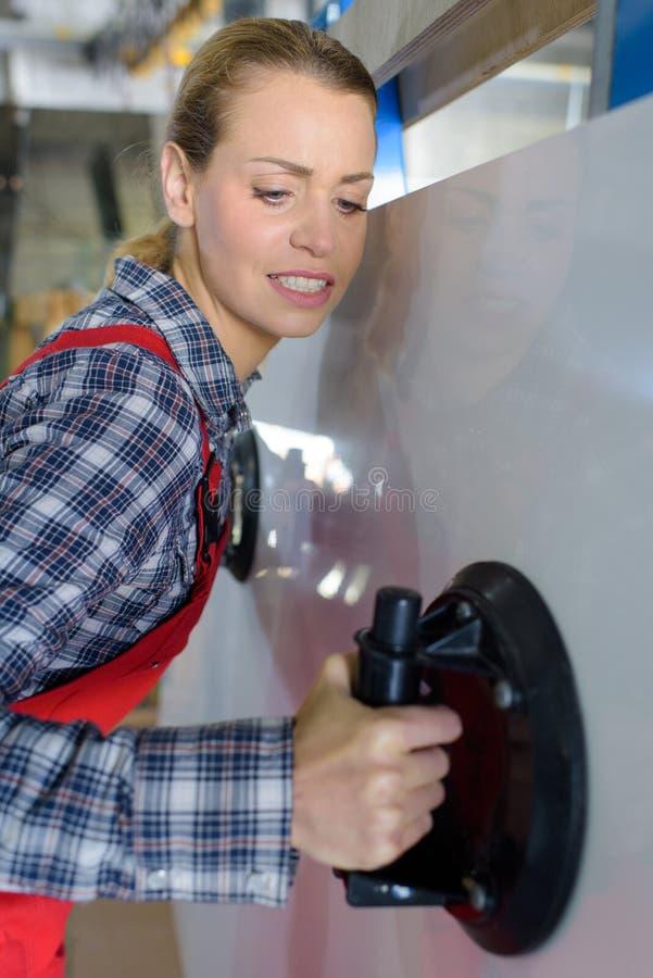 Vrouwelijke werknemer die zwaar materiaal in winkel dragen stock afbeelding