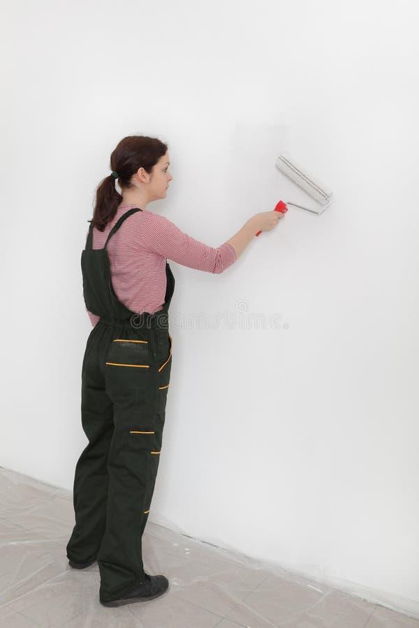 Vrouwelijke werknemer het schilderen muur in een ruimte stock afbeelding