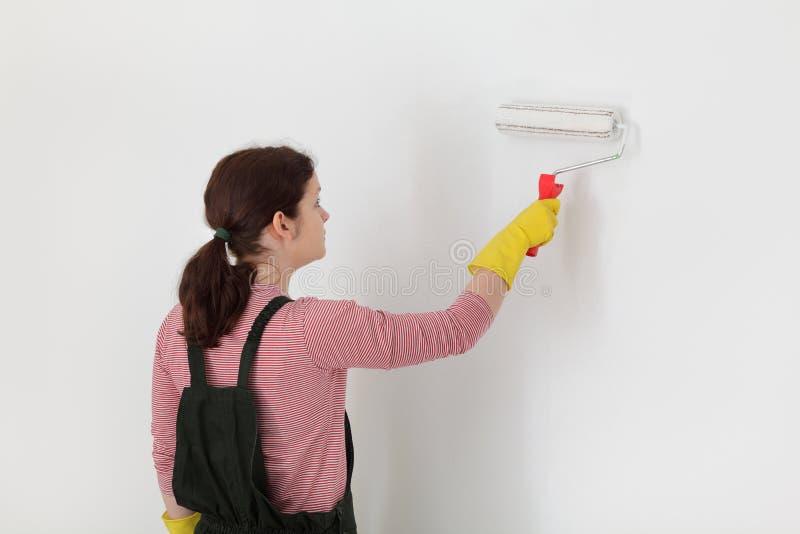 Vrouwelijke werknemer het schilderen muur in een ruimte royalty-vrije stock foto's