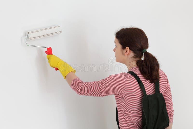Vrouwelijke werknemer het schilderen muur in een ruimte stock foto's