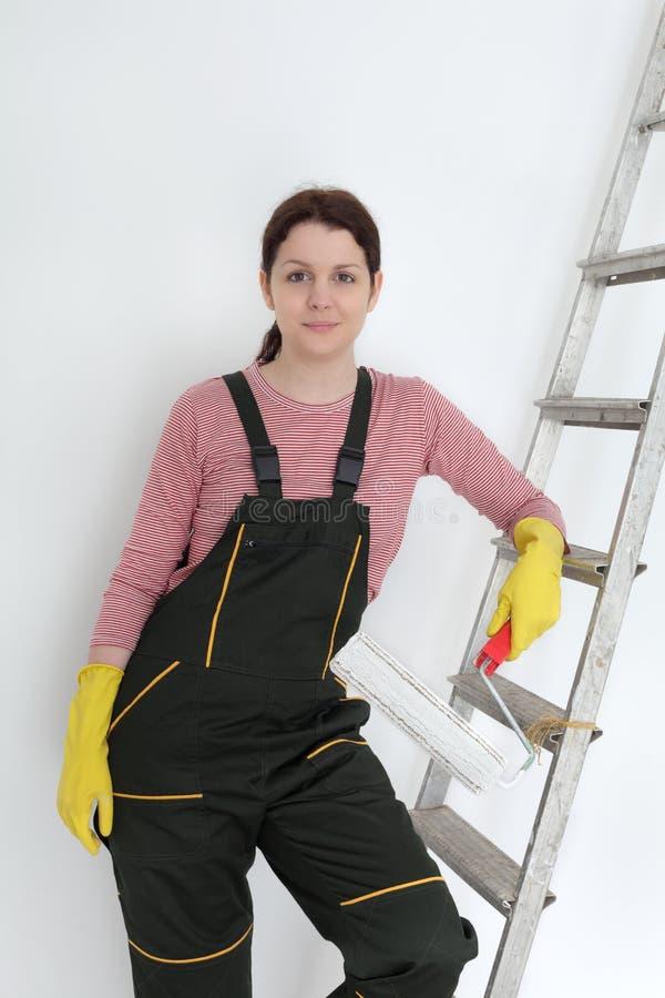 Vrouwelijke werknemer het schilderen muur in een ruimte royalty-vrije stock fotografie