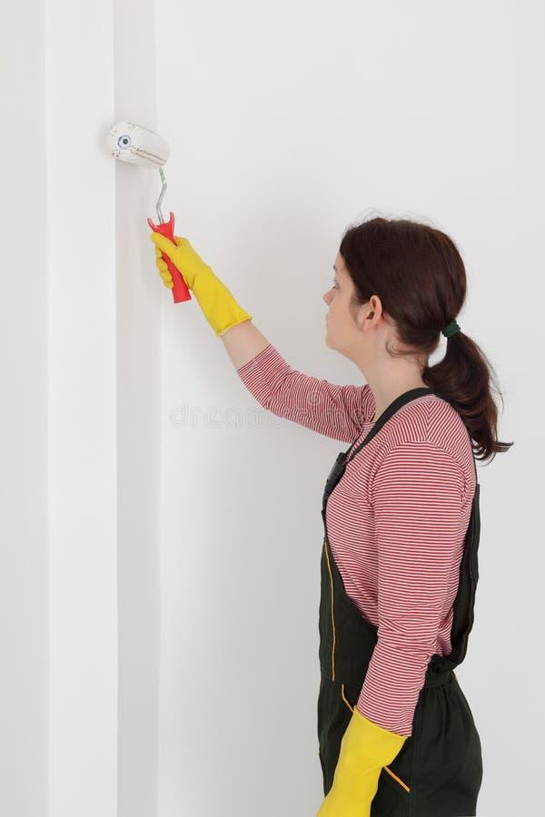 Vrouwelijke werknemer het schilderen muur in een ruimte stock foto