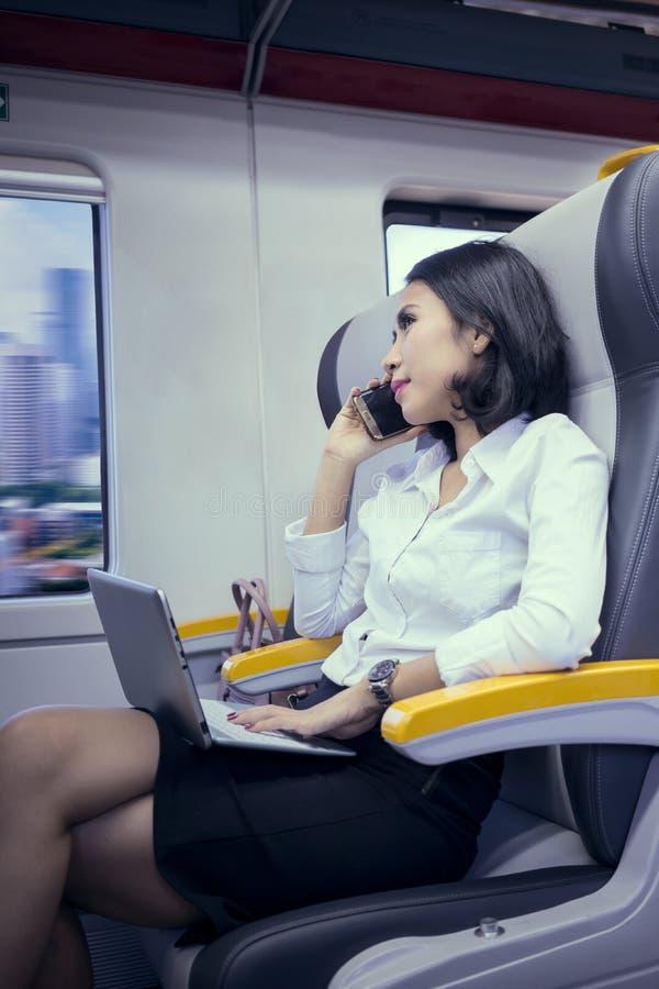 Vrouwelijke werknemer met laptop besprekingen op een telefoon stock fotografie