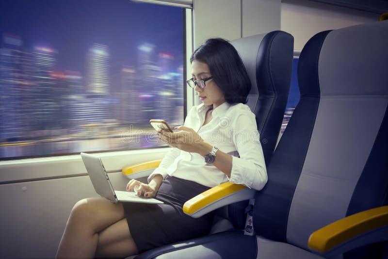 Vrouwelijke werknemer met laptop en telefoon aan de gang royalty-vrije stock afbeelding