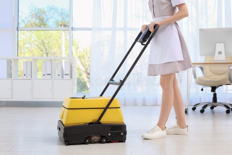Vrouwelijke werknemer met vloer schoonmakende machine stock afbeeldingen