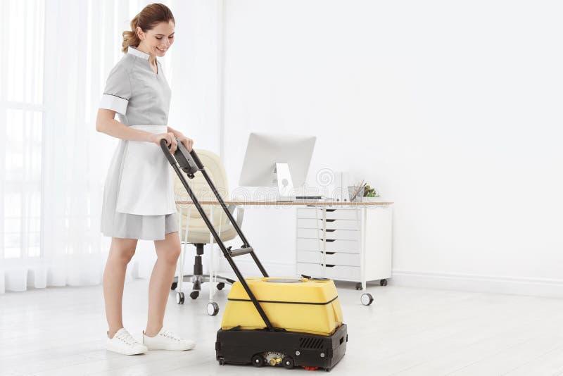 Vrouwelijke werknemer met vloer schoonmakende machine, binnen stock foto's