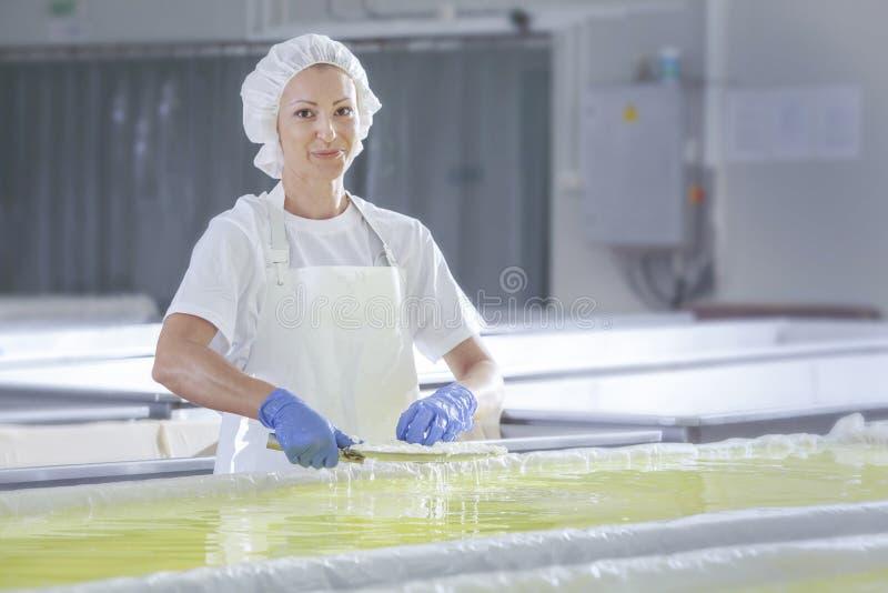 Vrouwelijke werknemer op witte feta-kaasproductielijn in een industr royalty-vrije stock foto's