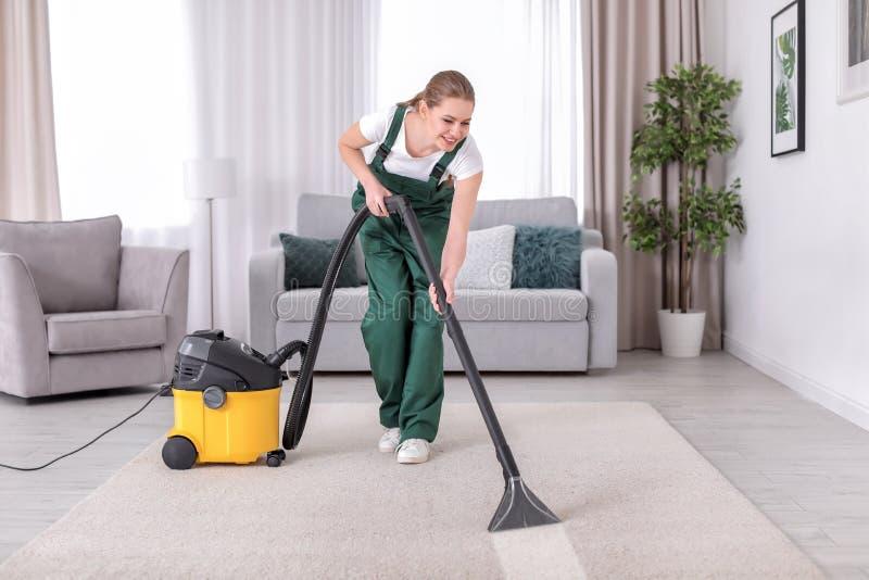 Vrouwelijke werknemer schoonmakend tapijt met vacuüm royalty-vrije stock afbeeldingen