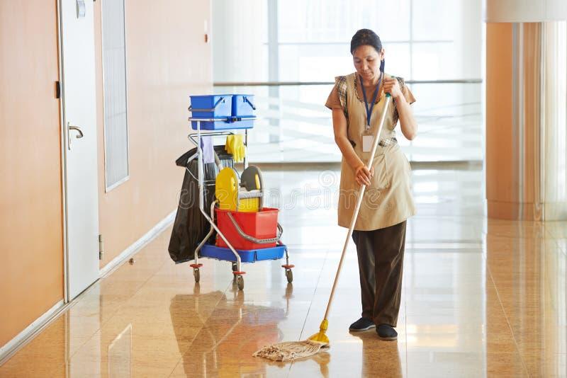 Vrouwelijke werknemer schoonmakende bedrijfszaal royalty-vrije stock fotografie