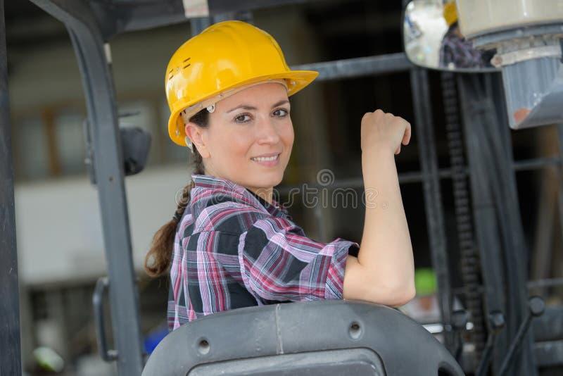 Vrouwelijke werknemer werkende vorkheftruck in het verschepen van werf stock fotografie