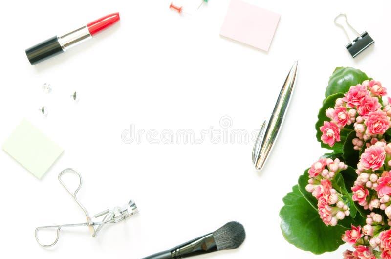 Vrouwelijke werkruimte met de bloeiende installatie van Kalanchoe, de maniertoebehoren van Vrouwen, kantoorbehoeftenlevering op w stock afbeelding