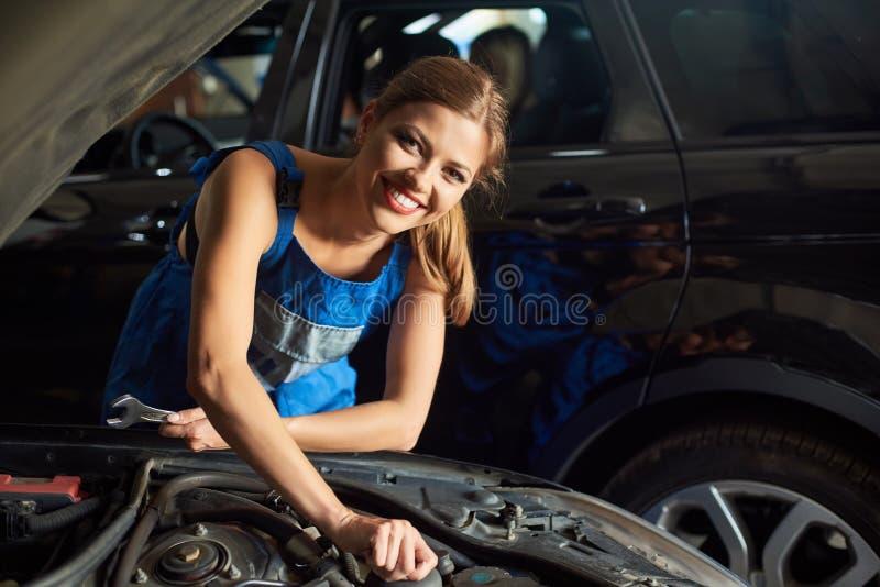 Vrouwelijke werktuigkundige die de zwarte auto herstellen royalty-vrije stock afbeelding