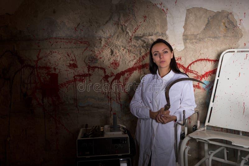 Vrouwelijke wetenschapper die grote ijzersikkel in kerker houden stock afbeeldingen