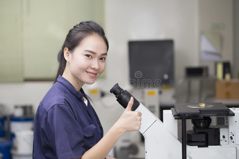 Vrouwelijke wetenschapper die in microscoop kijken royalty-vrije stock foto