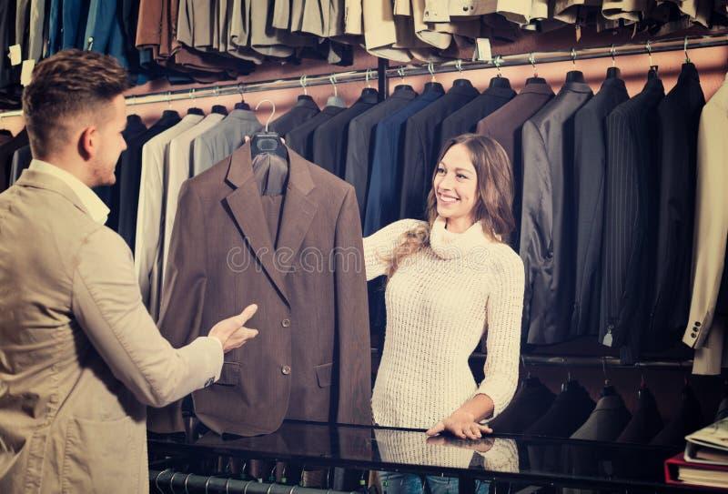 Vrouwelijke winkel hulp helpende klant om kostuum te kiezen royalty-vrije stock foto's