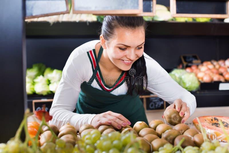 Vrouwelijke winkel hulp sorterende kiwien in kruidenierswinkelwinkel stock afbeeldingen