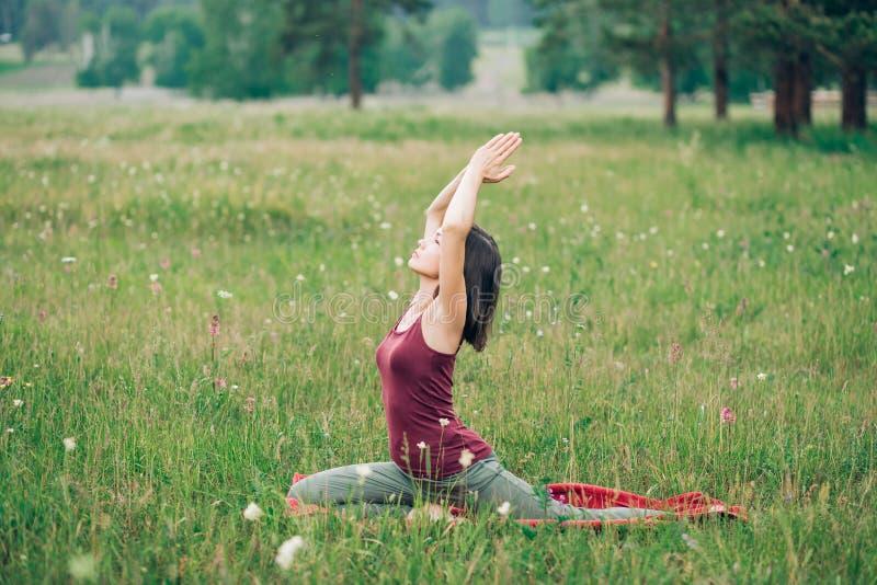 Vrouwelijke yoga in aard Jong aantrekkelijk donkerbruin meisje die oefeningen doen royalty-vrije stock foto