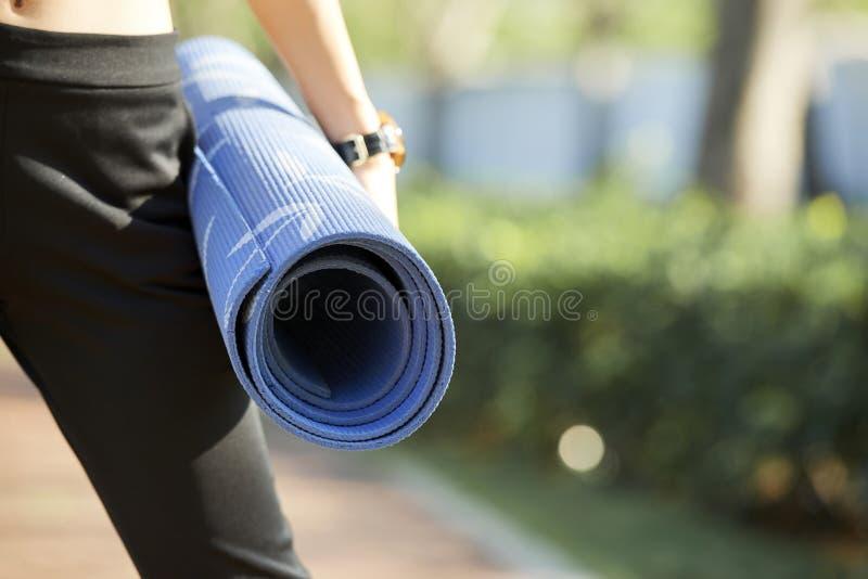 Vrouwelijke yogi met geschiktheidsmat stock foto