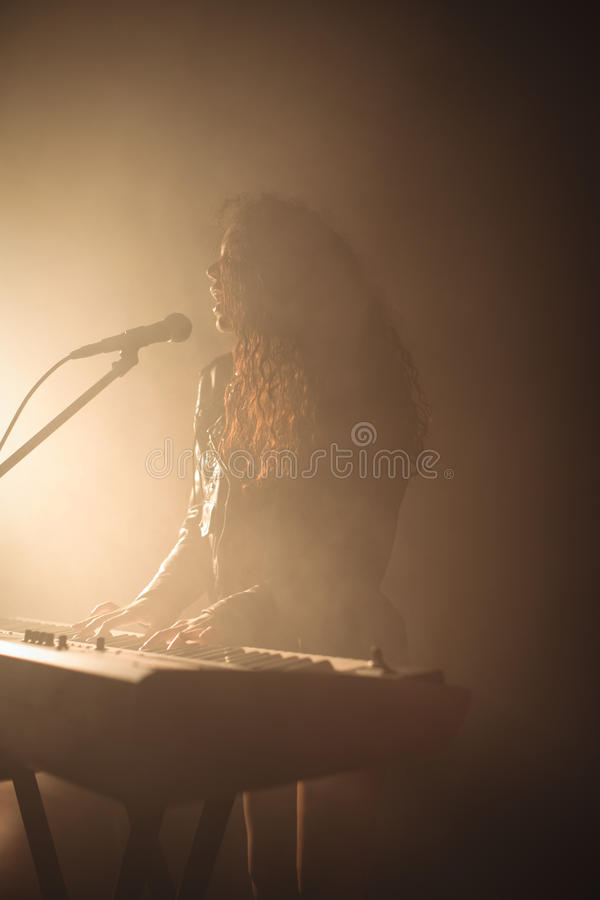 Vrouwelijke zanger met piano in verlichte nachtclub stock fotografie