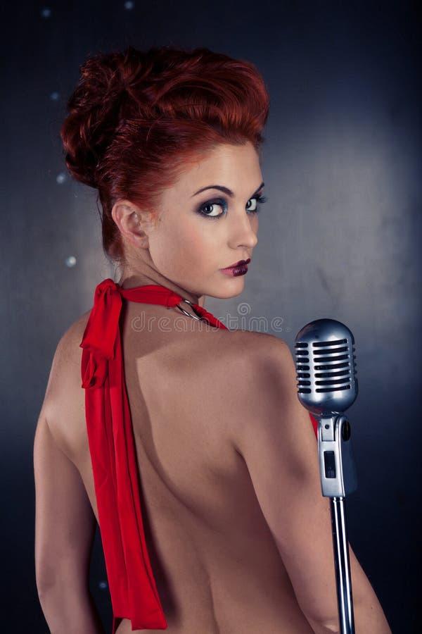 Vrouwelijke zanger rode kleding; uitstekende microfoon royalty-vrije stock afbeelding