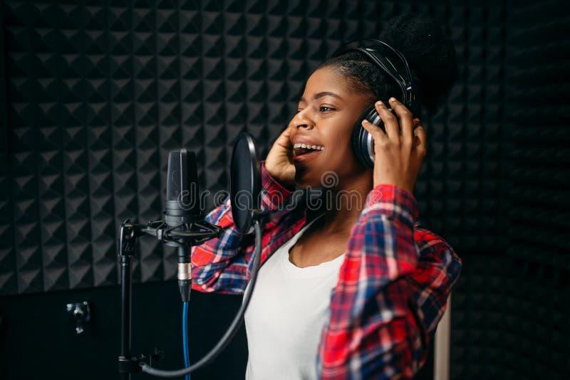 Vrouwelijke zangerliederen in audioopnamestudio royalty-vrije stock afbeeldingen