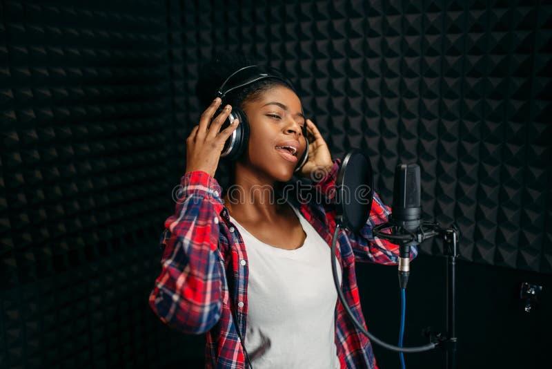 Vrouwelijke zangerliederen in audioopnamestudio stock foto's