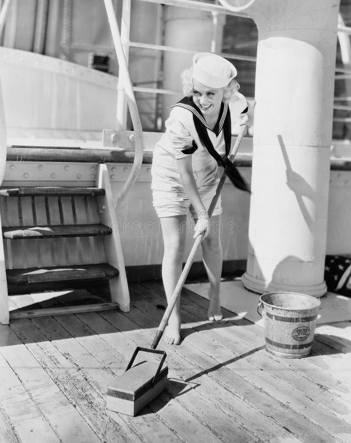 Vrouwelijke zeeman die sloependek zwabberen (Alle afgeschilderde personen leven niet langer en geen landgoed bestaat Leveranciers stock foto's