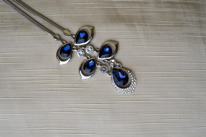 Vrouwelijke zilveren juwelen met blauwe gemmen, diamanten op een beige achtergrond in de hogere linkerhoek royalty-vrije stock fotografie